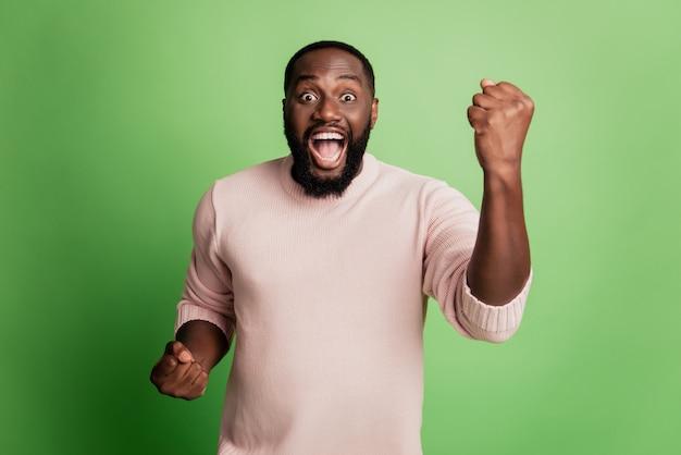Foto de um homem alegre e positivo levantando os punhos e vestindo uma camisa branca sobre fundo verde