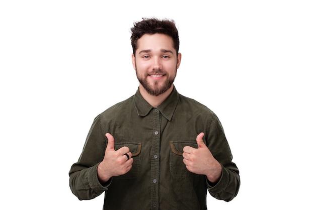 Foto de um homem alegre mostrando os polegares em pé sobre uma parede branca