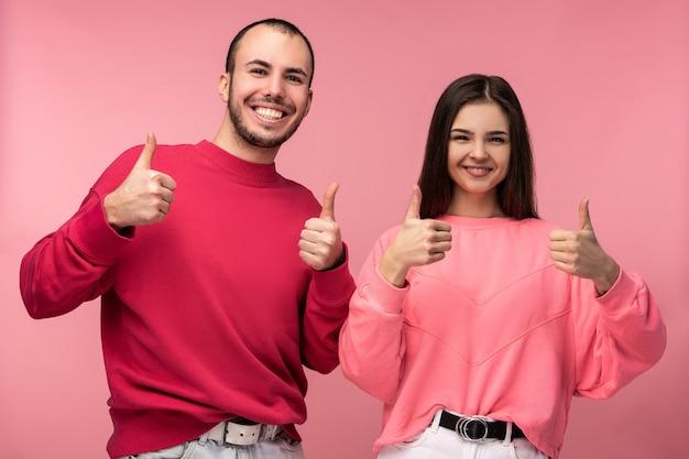 Foto de um homem atraente com barba em roupas vermelhas e mulher em rosa mostra o polegar e o sorriso, isolado sobre o fundo rosa.
