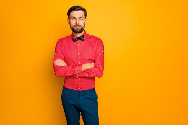Foto de um homem atraente homem de negócios com os braços cruzados, pessoa autoconfiante, trabalhador vestindo uma camisa vermelha elegante com calça azul de gravata borboleta preta