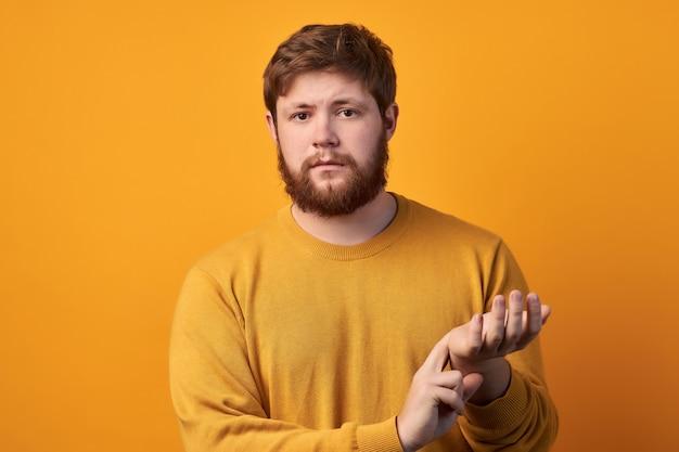 Foto de um homem atraente usa óculos redondos, mantém a mão no pulso, verifica o pulso ou os batimentos cardíacos, se preocupa com sua saúde, tem palpitações cardíacas, modelos contra um fundo branco