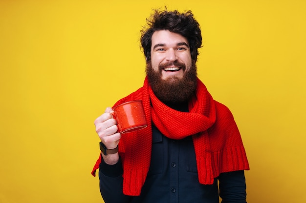 Foto de um homem barbudo bonito, usando um lenço vermelho, olhando para a câmera com um sorriso cheio de dentes e segurando uma caneca com uma bebida quente