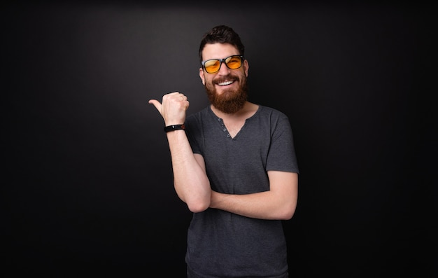 Foto de um homem barbudo com óculos de sol, fazendo sinal e sorrindo para a câmera