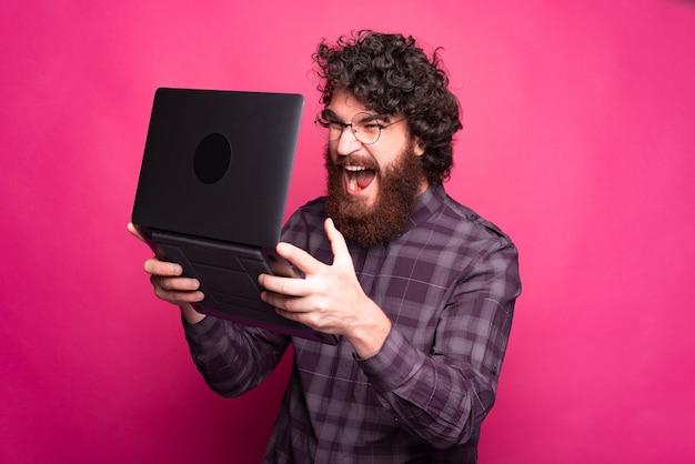 Foto de um homem barbudo com raiva olhando para o laptop e gritando