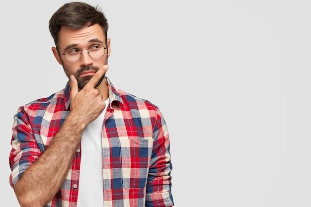 Foto de um homem barbudo de aparência agradável segura o queixo, olha pensativamente para o lado, segura o queixo, focado para o lado, fica de pé contra a parede branca