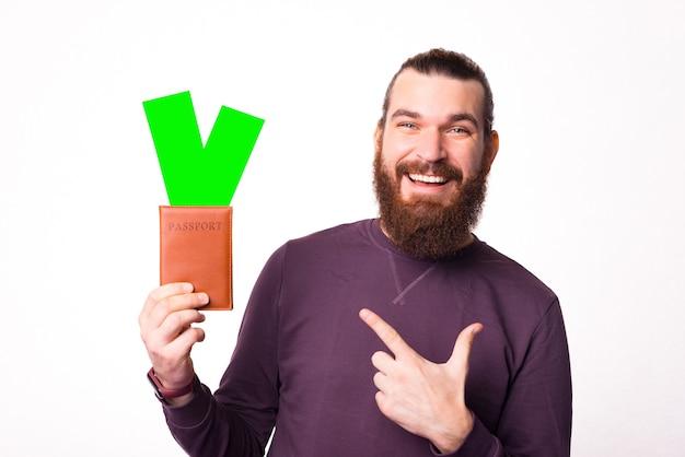 Foto de um homem barbudo e alegre segurando um passaporte com alguns ingressos apontando para eles