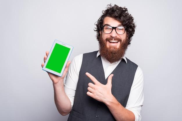 Foto de um homem barbudo espantado usando roupa casual e apontando para uma tela verde no tablet