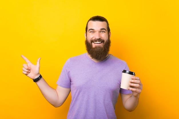 Foto de um homem barbudo feliz segurando uma xícara de bebida quente apontando para longe e sorrindo para a câmera
