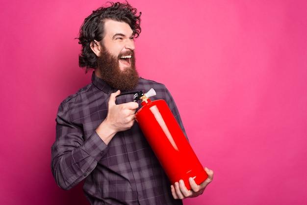 Foto de um homem barbudo gritando e usando o extintor de incêndio vermelho para parar o fogo