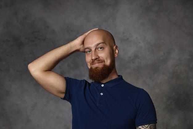 Foto de um homem barbudo jovem e atraente usando uma elegante camisa pólo com expressão sedutora, coçando a cabeça careca raspada, sentindo-se tímido ao falar com uma mulher bonita
