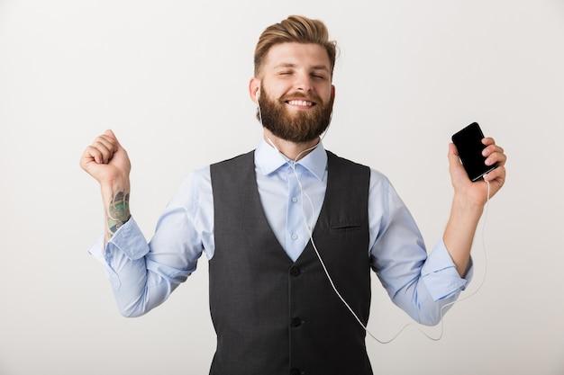 Foto de um homem barbudo jovem e bonito isolado sobre a parede branca, segurando a música do telefone móvel.