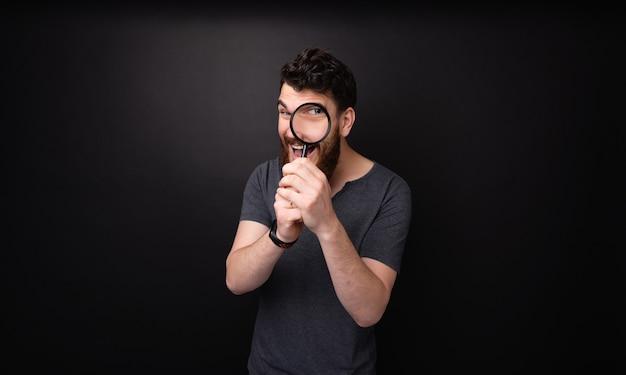 Foto de um homem barbudo se divertindo com uma lupa sobre fundo escuro