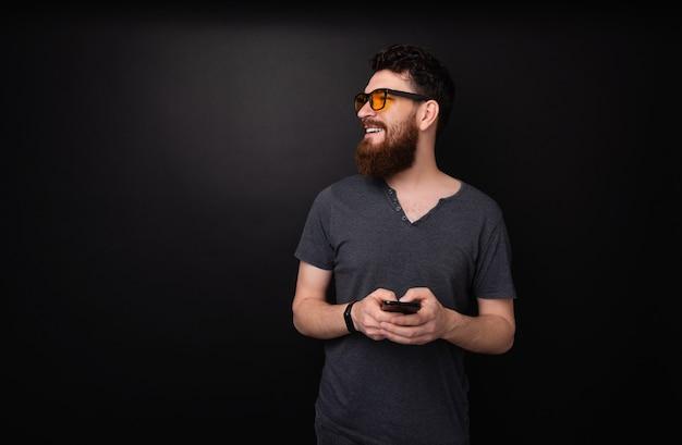 Foto de um homem barbudo segurando um telefone celular enquanto olha para longe, sobre um fundo cinza escuro