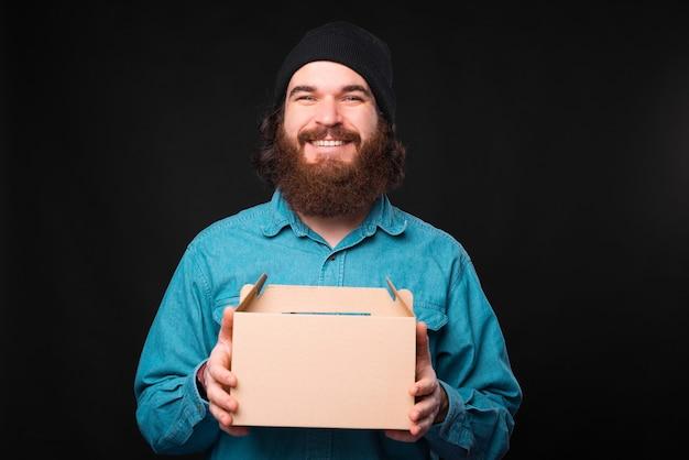 Foto de um homem barbudo segurando uma caixa de entrega sorrindo para a câmera perto de uma parede escura