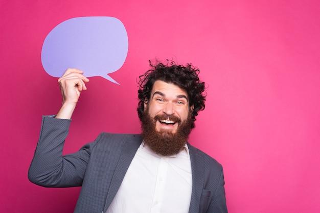 Foto de um homem barbudo sorridente em um balão de fala vazio segurando casual