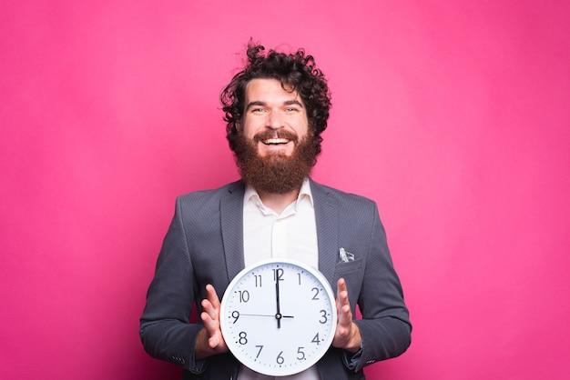 Foto de um homem barbudo sorridente, vestindo um terno casual, segurando um relógio branco