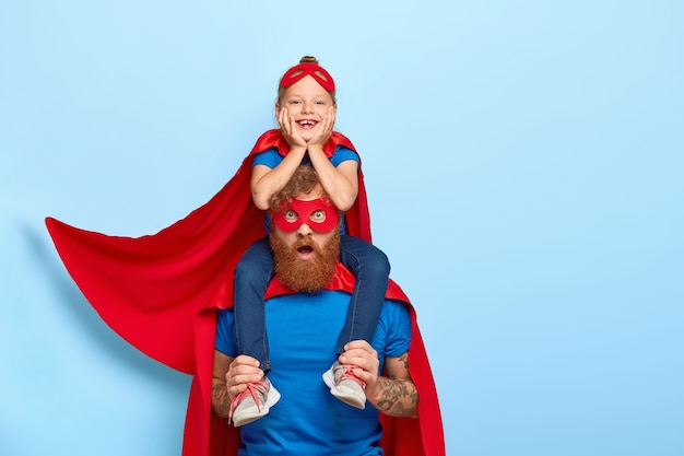Foto de um homem barbudo surpreso carregando uma filha pequena alegre no pescoço