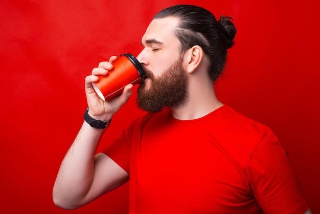 Foto de um homem bebendo café perto de uma parede vermelha