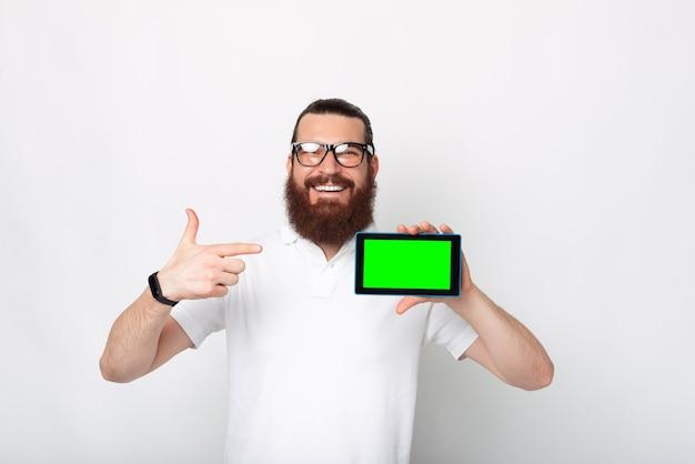 Foto de um homem bonito com barba sorrindo e apontando para a tela verde do tablet sobre fundo branco