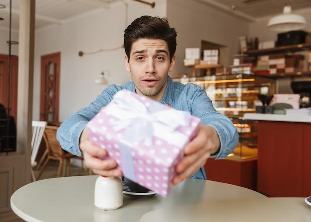 Foto de um homem bonito dando uma caixa de presente, enquanto está sentado à mesa em um café ou padaria