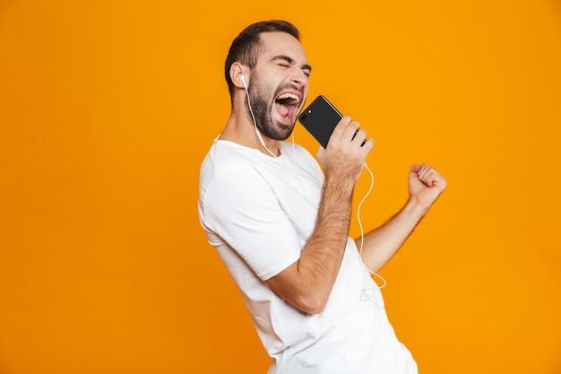 Foto de um homem bonito dos anos 30 cantando enquanto usa fones de ouvido e telefone celular, isolada