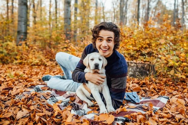 Foto de um homem bonito e seu cachorro passam um tempo na floresta de outono.