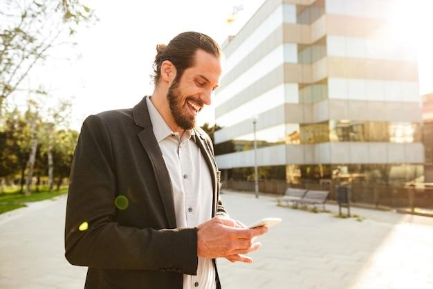 Foto de um homem branco satisfeito em um terno formal sorrindo e usando um smartphone, em pé perto de um prédio de escritórios