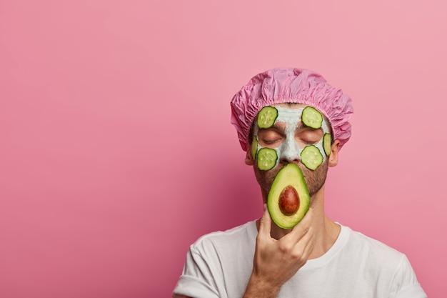 Foto de um homem calmo e satisfeito desfrutando de tratamentos de beleza em um salão de spa, segura abacate, usa máscara vegetal, faz procedimentos de cosmetologia