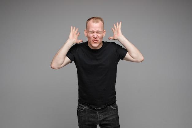 Foto de um homem caucasiano com as mãos perto da cabeça, isolada na parede cinza