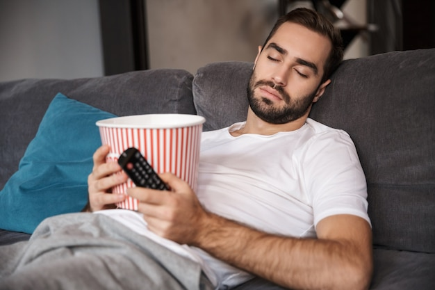 Foto de um homem caucasiano de 30 anos vestindo uma camiseta casual segurando um balde de pipoca enquanto dorme no sofá da sala de estar