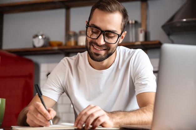 Foto de um homem caucasiano dos anos 30 usando óculos escrevendo notas enquanto usa um laptop prateado na mesa da cozinha