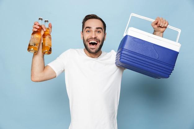 Foto de um homem caucasiano feliz em uma camiseta branca casual rindo enquanto carregava uma caixa térmica com garrafas de cerveja durante a festa de verão isolada sobre a parede azul