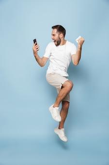 Foto de um homem caucasiano positivo em uma camiseta branca casual, regozijando-se enquanto segura o cartão de crédito e o smartphone isolados sobre a parede azul