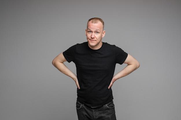 Foto de um homem caucasiano vestindo uma camiseta e jeans isolado na parede cinza