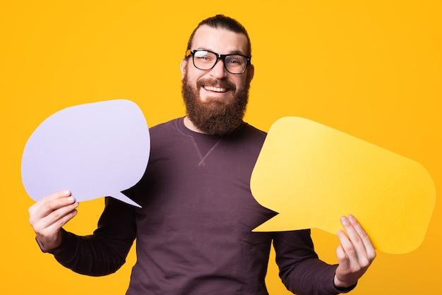 Foto de um homem com barba usando óculos segurando dois balões de fala