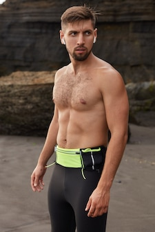 Foto de um homem confiante com expressão pensativa, vestido com leggigs pretas e corpo musculoso