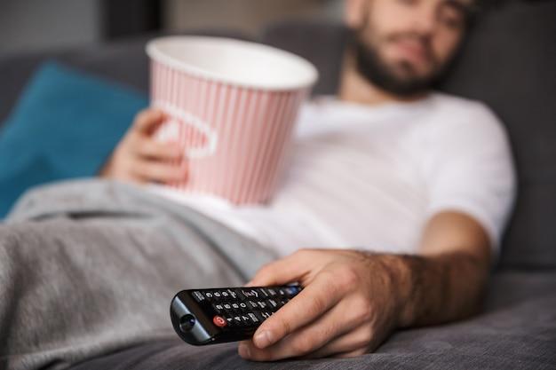 Foto de um homem de 30 anos com a barba por fazer, vestindo uma camiseta casual segurando um balde de pipoca enquanto dorme no sofá da sala de estar