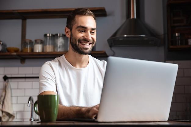 Foto de um homem de 30 anos com a barba por fazer, vestindo uma camiseta casual usando um laptop prateado enquanto está sentado à mesa em um apartamento moderno
