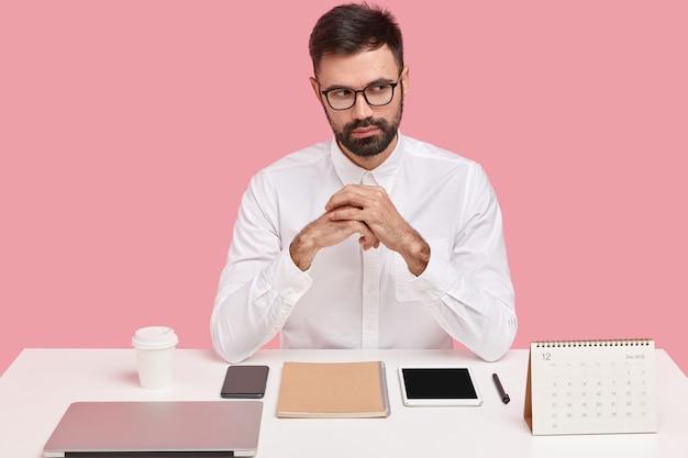 Foto de um homem de negócios bonito e barbudo tem uma expressão atenciosa, mantém as mãos juntas, vestido com roupa formal, tem tudo em seus lugares na mesa