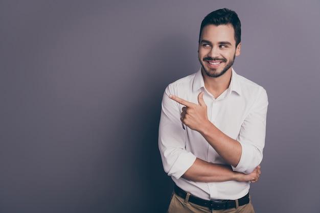 Foto de um homem de negócios bonito e sorridente, indicando o espaço vazio do dedo