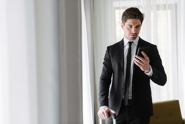 Foto de um homem de negócios bonito perplexo vestindo um terno preto, digitando no celular e segurando a bagagem em um apartamento de hotel