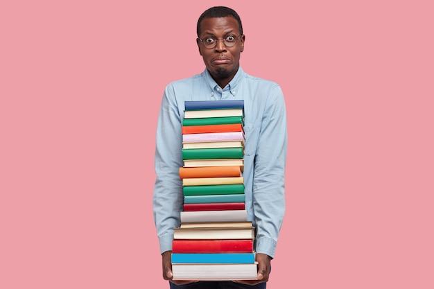 Foto de um homem de pele escura intrigado e insatisfeito segurando uma pilha pesada de livros, vestindo uma camisa formal, modelos sobre a parede rosa do estúdio