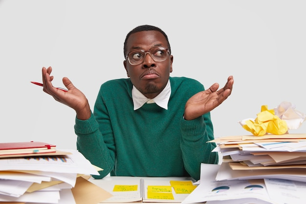 Foto de um homem de pele escura sem noção dando de ombros com hesitação, não consigo decidir qual investidor escolher, trabalha com papelada no espaço de coworking