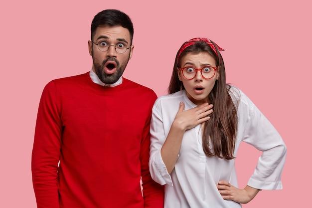 Foto de um homem e uma mulher caucasianos estupefatos olhando com grande espanto, notando algo inacreditável, prendendo a respiração, vestidos casualmente