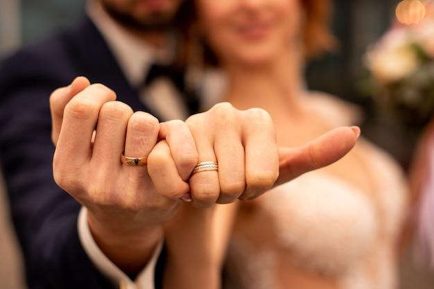 Foto de um homem e uma mulher com aliança de casamento, segurando os dedos