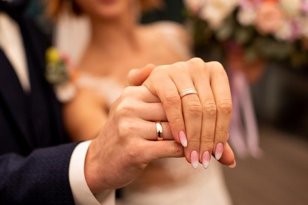 Foto de um homem e uma mulher com aliança de casamento, segurando os dedos Foto Premium