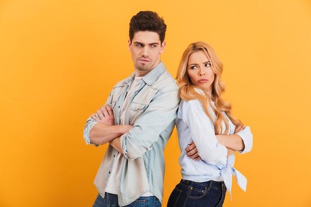 Foto de um homem e uma mulher ressentidos em roupas jeans, em pé, costas com costas, em uma briga, isolada sobre a parede amarela