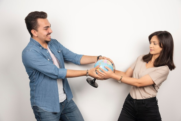 Foto de um homem e uma mulher segurando o globo terrestre.