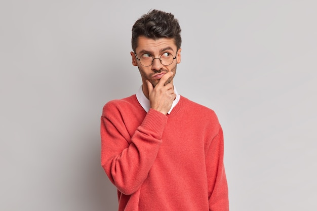 Foto de um homem europeu adulto bonito e pensativo segurando o queixo e olhando pensativamente para longe, tentando resolver o problema