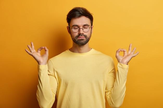 Foto de um homem europeu com a barba por fazer relaxado em pose de lótus, faz gesto zen, respira profundamente e tenta relaxar, mantém os olhos fechados, usa óculos e macacão, posa dentro de casa, atinge o nirvana